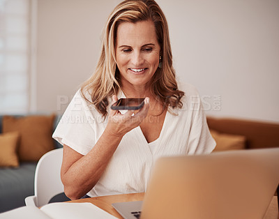 Buy stock photo Shot of a mature businesswoman talking on a cellphone while using a laptop in an office