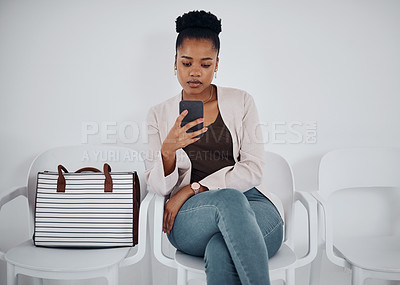 Buy stock photo Shot of a young businesswoman using a cellphone while sitting in a line against a white background