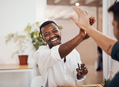 Buy stock photo Shot of two businessmen giving each other a high five in an office