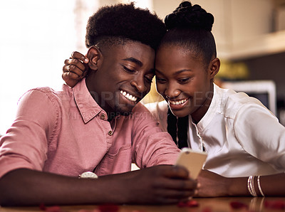 Buy stock photo Cropped shot of an affectionate young couple using a smartphone together on in their kitchen at home
