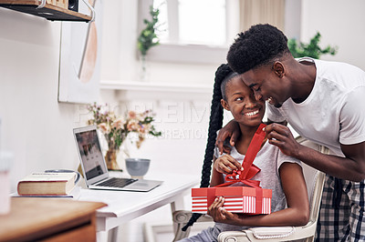 Buy stock photo Shot of a young man surprising his girlfriend with a present at home