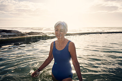 Buy stock photo Portrait of a cheerful senior woman enjoying herself while swimming outdoors in the ocean