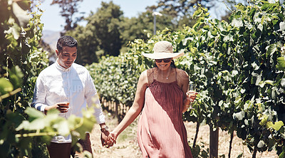 Buy stock photo Shot of a young couple having a glass of wine while walking through a vineyard