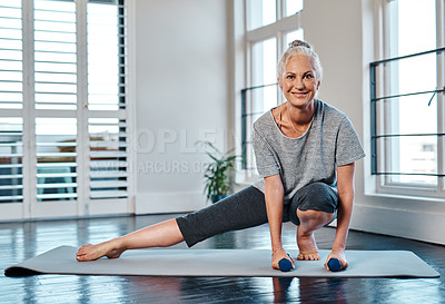 Buy stock photo Portrait of a cheerful mature woman practicing yoga while making use of weights inside of a studio during the day
