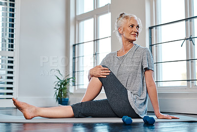 Buy stock photo Shot of a cheerful mature woman practicing yoga inside of a studio during the day