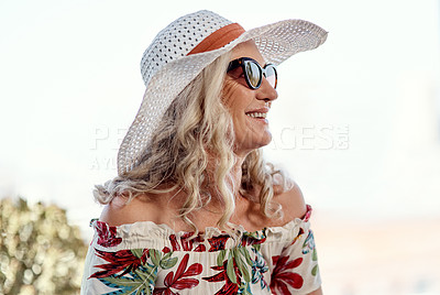 Buy stock photo Cropped shot of an attractive senior woman smiling while sitting outdoors on a summer's day