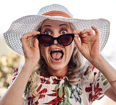Buy stock photo Cropped portrait of an attractive senior woman looking surprised while wearing sunglasses outdoors
