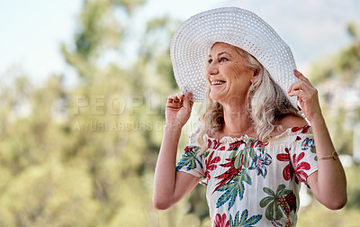 Buy stock photo Cropped shot of an attractive senior woman smiling while standing outdoors on a summer's day