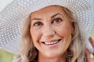 Buy stock photo Cropped portrait of an attractive senior woman smiling while standing outdoors on a summer's day