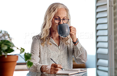 Buy stock photo Cropped shot of an attractive senior businesswoman drinking coffee while working from home