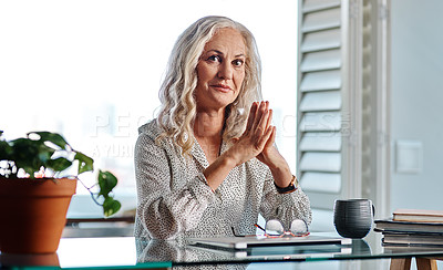 Buy stock photo Cropped portrait of an attractive senior businesswoman sitting with her hands together while working from home