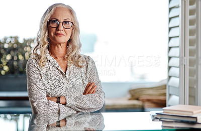 Buy stock photo Cropped portrait of an attractive senior businesswoman sitting with her arms crossed while working from home