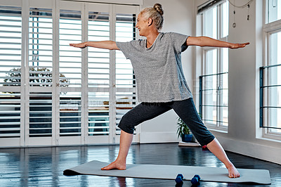 Buy stock photo Shot of a relaxed mature woman practicing yoga inside of a studio during the day