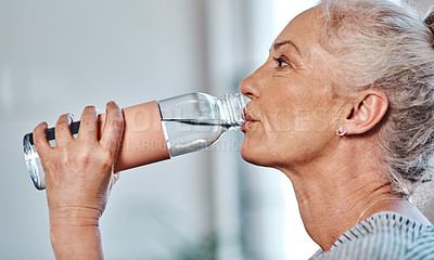 Buy stock photo Closeup of a mature woman having a drink of water inside of a studio during the day
