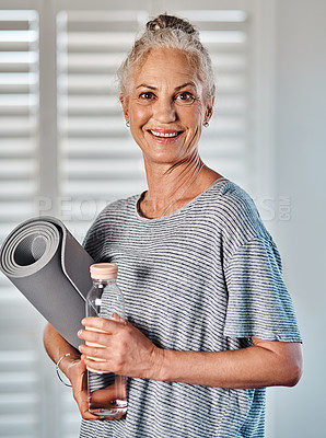 Buy stock photo Portrait of a cheerful mature woman holding a bottle of water and yoga mat ready to start her morning session of yoga inside of a studio