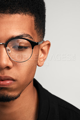 Buy stock photo Cropped studio shot of a handsome young man wearing glasses and contemplating while standing against a grey background