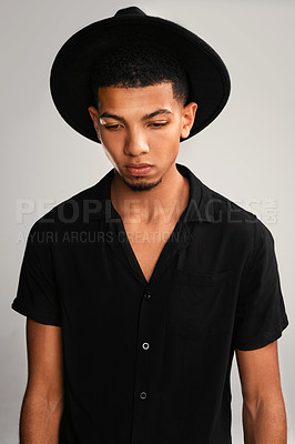 Buy stock photo Cropped studio shot of a handsome young man wearing a hat and contemplating while standing against a grey background