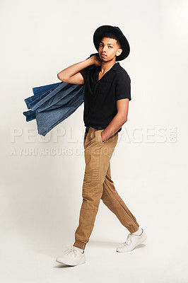 Buy stock photo Portrait of a handsome young man wering a hat and holding a jacket while posing against a grey background