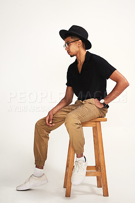 Buy stock photo Studio shot of a handsome young man wearing a hat and glasses while being seated on a chair against a grey background inside of a studio