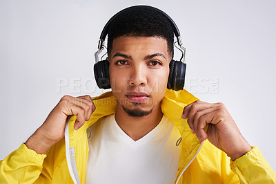 Buy stock photo Portrait of a handsome young man listing to musing on his headphones while standing against a grey background inside of a studio