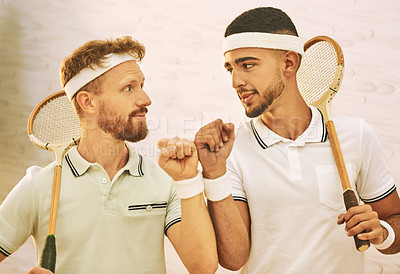 Buy stock photo Shot of two young men fist bumping before playing a game of squash