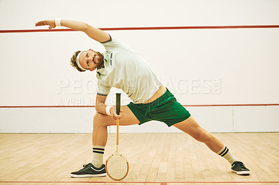 Buy stock photo Shot of a young man stretching before playing a game of squash