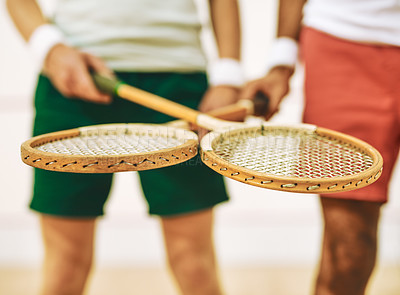 Buy stock photo Cropped shot of two men crossing their racquets at a squash court