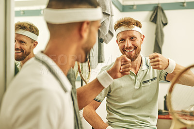 Buy stock photo Shot of two young men fist bumping in the locker room after a game of squash