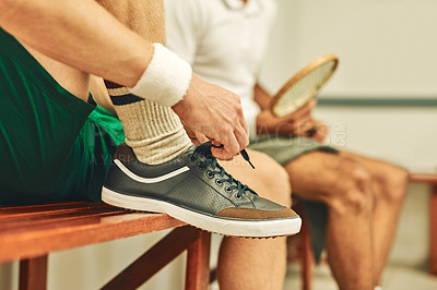 Buy stock photo Cropped shot of a man putting on his trainers in the locker room before a game of squash