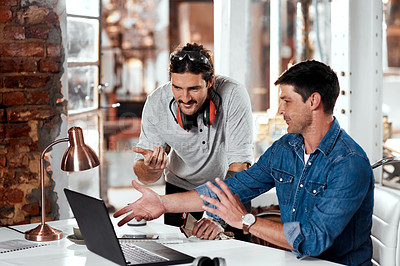 Buy stock photo Cropped shot of two young businessmen working together on a laptop in an office inside their workshop