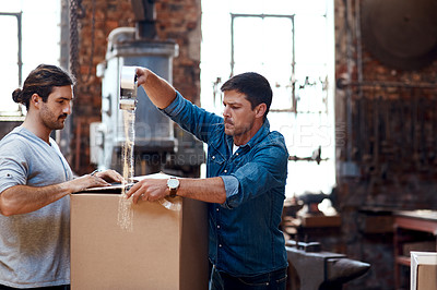 Buy stock photo Cropped shot of two young businessmen wrapping a cardboard box together while sorting out orders and deliveries inside their workshop