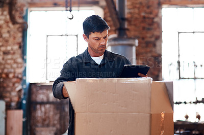 Buy stock photo Cropped shot of a young businessman using a digital tablet while sorting out orders and deliveries inside his workshop