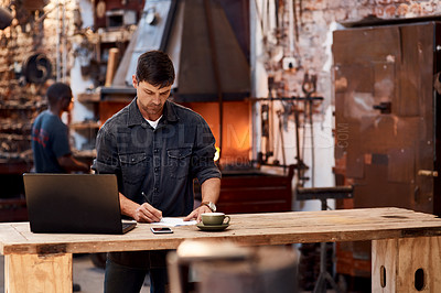 Buy stock photo Cropped shot of a handsome young businessman working on a laptop inside his workshop
