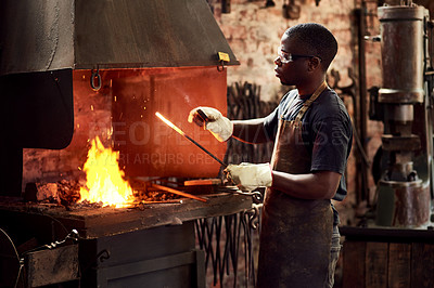 Buy stock photo Cropped shot of a handsome young metal worker sharpening a hot metal rod inside a welding workshop