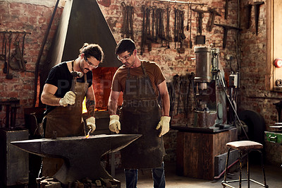 Buy stock photo Cropped shot of two handsome young metal workers working together inside a welding workshop