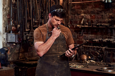 Buy stock photo Cropped shot of a handsome young craftsman using a digital tablet while working inside a metal workshop