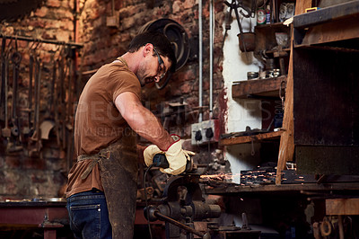 Buy stock photo Cropped shot of a handsome young metal worker using a blowtorch while working inside a welding workshop