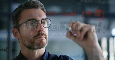 Buy stock photo Shot of a mature businessman writing notes on a glass wall in an office