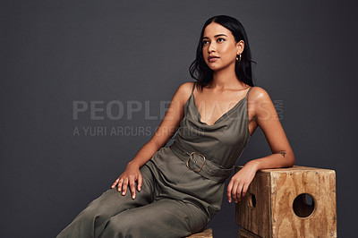 Buy stock photo Cropped shot of an attractive young woman wearing a formal dress and sitting against a dark background in the studio