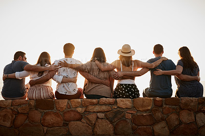 Buy stock photo Rearview shot of a group of unrecognizable friends embracing each other while sitting together at the beach