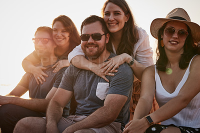 Buy stock photo Cropped portrait of a group of young friends smiling while sitting together at the beach