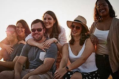 Buy stock photo Cropped portrait of a group of young friends smiling while hanging out together together at the beach