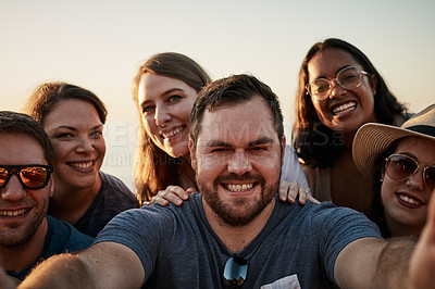 Buy stock photo Cropped portrait of a group of young friends taking a selfie together at the beach during the day