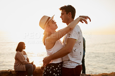 Buy stock photo Cropped shot of an affectionate young couple embracing each other while standing at the beach at sunset