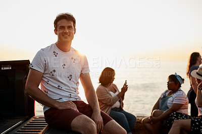 Buy stock photo Cropped portrait of a handsome young man smiling while sitting at the beach with his friends in the background