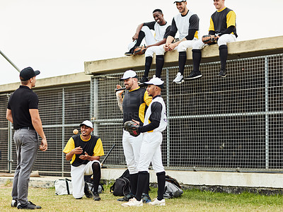 Buy stock photo Full length shot of a young baseball coach talking to his team during a training session on the pitch outdoors