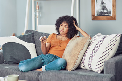 Buy stock photo Shot of a young woman watching tv at home