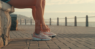 Buy stock photo Cropped shot of an unrecognizable young woman tying up her shoelaces while working out near the beach