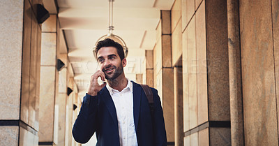 Buy stock photo Cropped shot of a cheerful young man talking on his cellphone while walking to work outside during the day