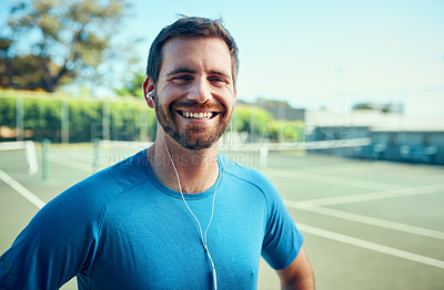 Buy stock photo Portrait of a sporty young man listening to music while exercising on a tennis court